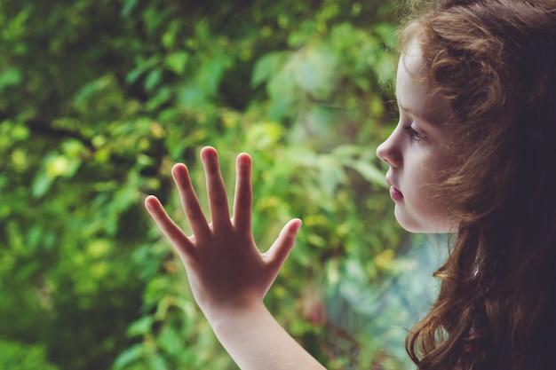 Smutne dziecko patrząc przez okno.