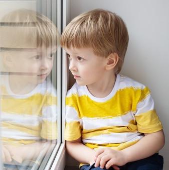 Smutne dziecko siedzi na oknie.
