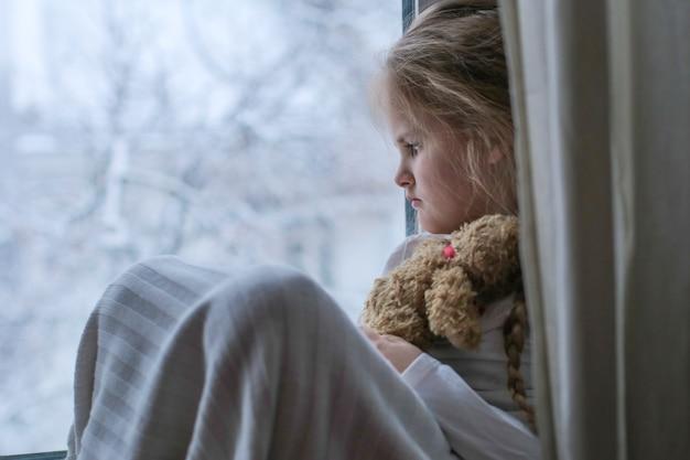Smutne dziecko trzyma zabawkę i wygląda przez okno