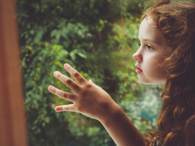 Smutne dziecko wyglądające przez okno.