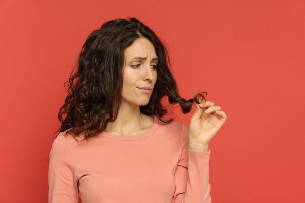 Smutne kobiece spojrzenie na rozdwojone końcówki włosów kręcona brunetka potrzebuje fryzury lub profesjonalnego leczenia