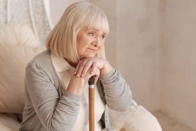 Smutne myśli. nieszczęśliwa, przygnębiona starsza kobieta wsparta na lasce i zamyślona w fotelu