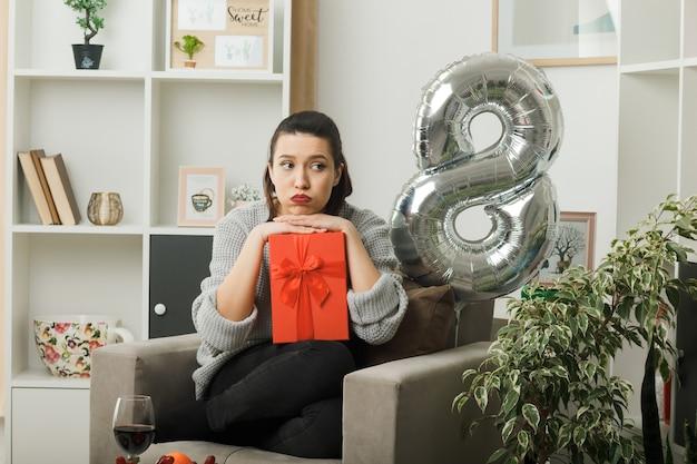 Smutne nadęte policzki piękna dziewczyna na szczęśliwy dzień kobiet trzymająca prezent siedzący na fotelu w salonie
