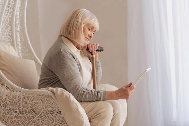 Smutne wspomnienia. moody przygnębiona starsza kobieta trzymająca zdjęcie i patrząc na siedzącą w fotelu