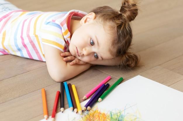 Smutne, zmęczone, sfrustrowane, znudzone, stresujące dziecko leży na drewnianej podłodze z białą kartką papieru i kredkami. trudności w nauce, koncepcja edukacji. relacje rodzinne. tęskni za domem