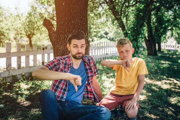 Smutni i zdenerwowani faceci siedzą na kolanach i trzymają duże kciuki w dół.