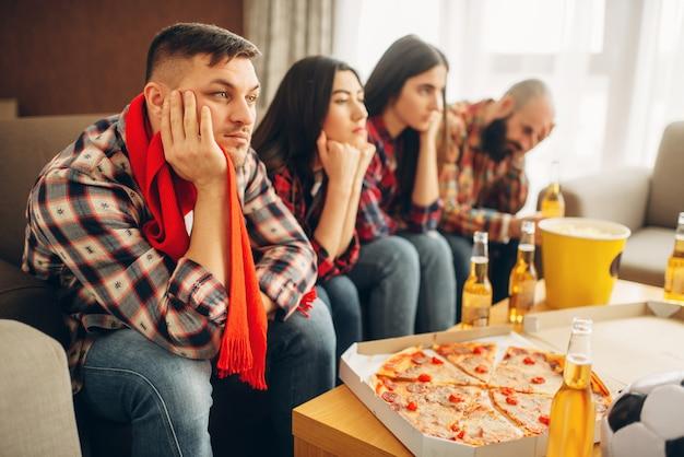 Smutni przyjaciele oglądają telewizję na nudnej imprezie w domu. zła przyjaźń, grupa znudzonych ludzi wypoczywa razem