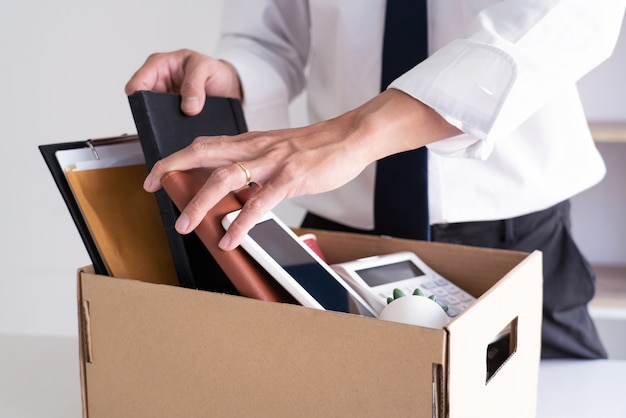Smutni zwolnieni młodzi biznesmeni-pracownicy trzymają pudła, w tym rośliny doniczkowe i dokumenty na bezrobocie rzeczy osobistych, zrezygnowana koncepcja.