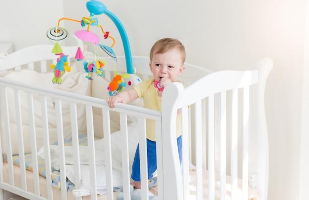 Smutny 10-miesięczny chłopiec płacze i trzyma się z boku łóżeczka