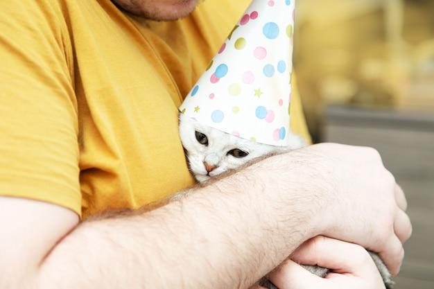 Smutny biały kotek w świątecznym kapeluszu w ramionach młodego mężczyzny. koncepcja urodziny i wakacje.