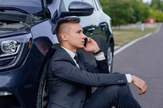 Smutny biznesmen używa smartfona siedząc na drodze w pobliżu zepsutego samochodu, otworzył maskę