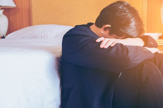 Smutny biznesowy mężczyzna siedzi w pokoju hotelowym