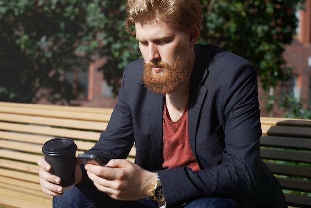 Smutny brodacz używa telefonu, aby znaleźć nową pracę