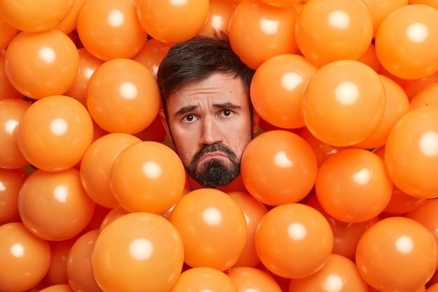 Smutny brodaty dorosły mężczyzna ściąga usta niezadowolony wyraz twarzy wystaje głowa napompowane pomarańczowe balony