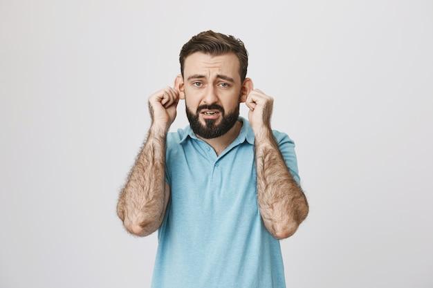 Smutny brodaty facet pokazujący uszy i narzekający