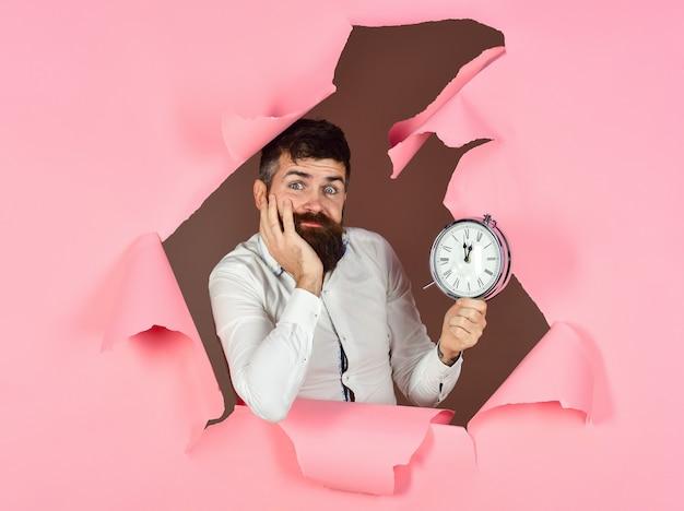 Smutny brodaty mężczyzna trzyma zegar mężczyzna spóźnia się patrząc przez dziurę w różowym papierze tracąc czas spóźniony termin