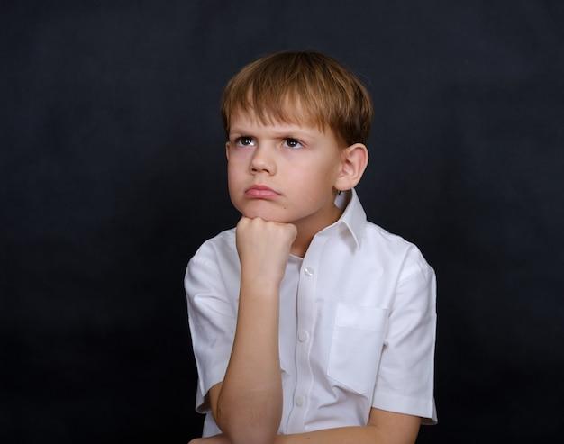 Smutny chłopak o wyglądzie europejczyka ze łzami w oczach. izolować na czarno