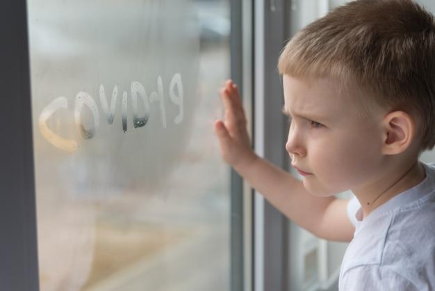 Smutny chłopak patrząc przez okno