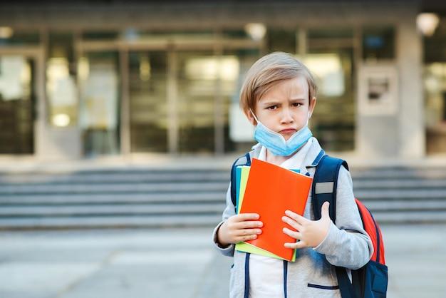 Smutny chłopak w masce idzie do szkoły.