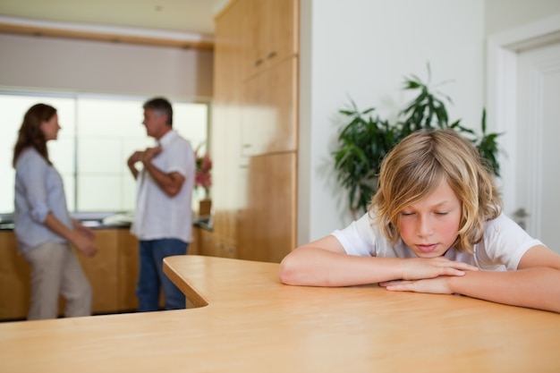 Smutny chłopiec musi słuchać walczących rodziców