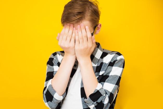 Smutny chłopiec nastolatek na sobie ubranie stojące przed żółtym