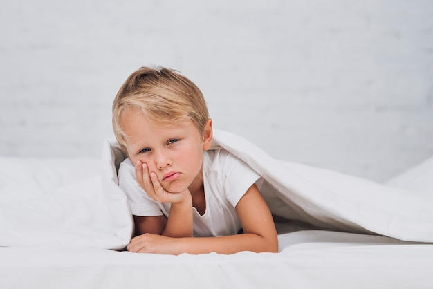 Smutny chłopiec przebywa w łóżku