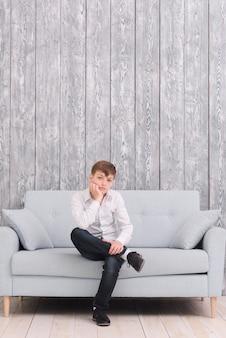 Smutny chłopiec siedzi na kanapie w domu patrząc na kamery