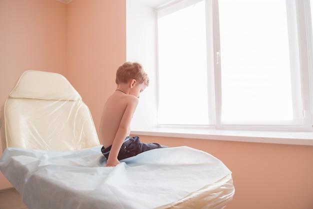 Smutny chłopiec siedzieć w szpitalnej kanapie