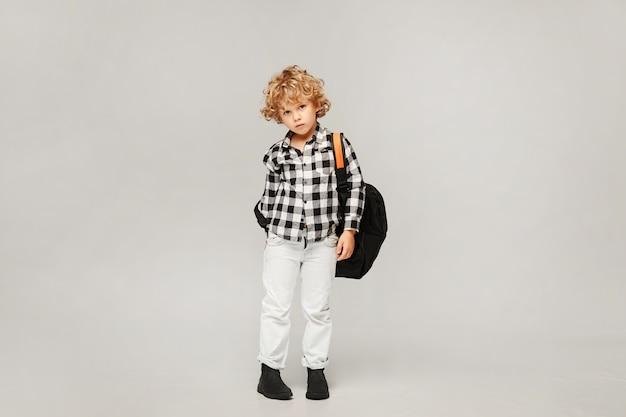 Smutny chłopiec w koszuli i dżinsy z plecakiem na białym tle.