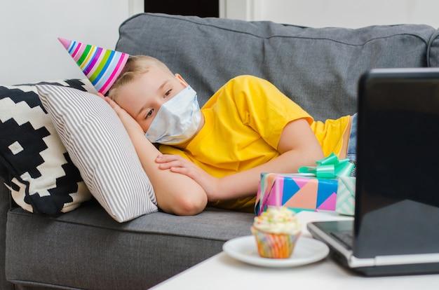 Smutny chłopiec w masce medycyny świętuje urodziny przez połączenie wideo z laptopem