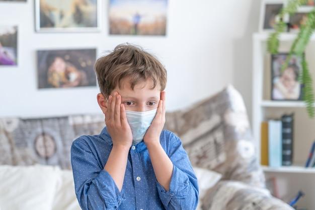 Smutny chłopiec w masce medycznej. pojęcie kwarantanny i ochrony przed zanieczyszczonym powietrzem