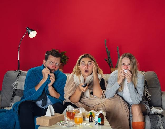 Smutny. chorzy młodzi ludzie z gorączką i zimnem patrzą na cierpienie. czuję się chory, siny, wciągający nosem. zimno, wirus, grypa sezonowa. mężczyzna i kobieta siedzi na kanapie z miodem, herbatą, tabletkami w domu razem.