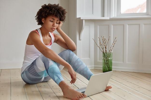 Smutny ciemnoskóry student ubrany w zwykły strój siedzi boso na drewnianej podłodze w pustym pokoju z komputerem przenośnym