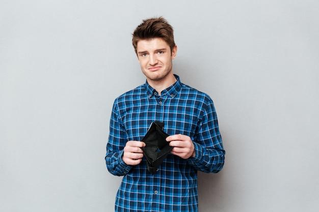 Smutny człowiek stojący nad szarej ściany gospodarstwa portfel bez pieniędzy.