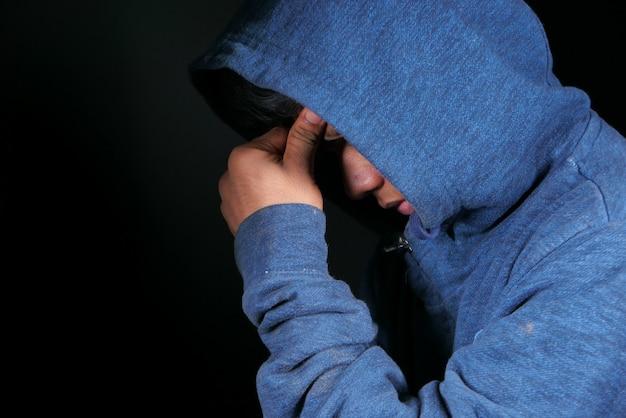 Smutny człowiek w kaptur pokrywa twarz z rękami odizolowanymi w kolorze czarnym.