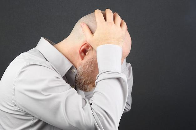 Smutny człowiek z rękami zamkniętymi twarz