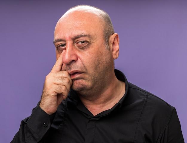 Smutny dorosły chory kaukaski mężczyzna kładzie palec na powiece na białym tle na fioletowej ścianie z miejsca na kopię