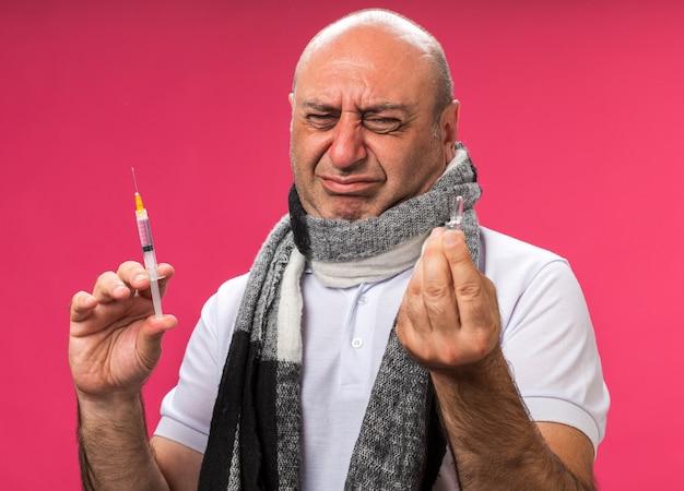 Smutny dorosły chory kaukaski mężczyzna z szalikiem na szyi trzymający strzykawkę i patrzący na ampułkę odizolowaną na różowej ścianie z kopią przestrzeni