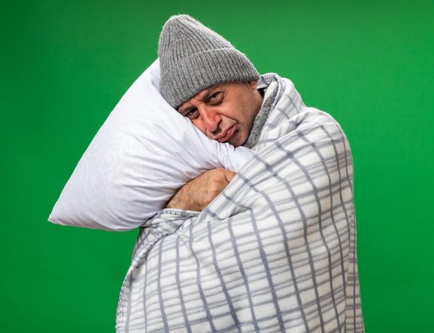 Smutny dorosły chory kaukaski mężczyzna z szalikiem na szyi w czapce zimowej owiniętej w kratę trzymający głowę i kładący głowę na poduszce odizolowany na zielonej ścianie z miejscem na kopię