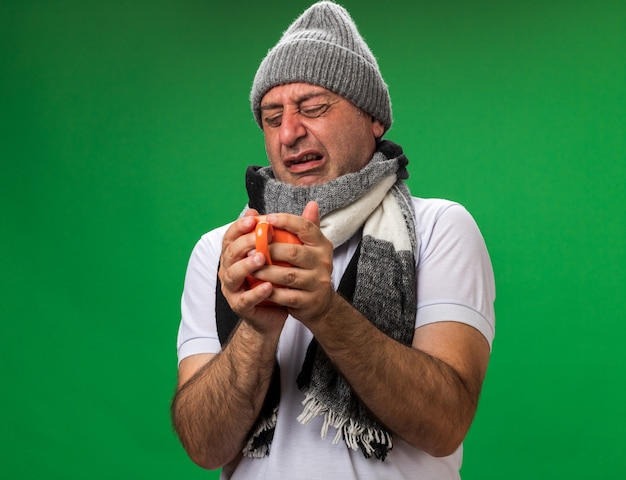 Smutny dorosły chory kaukaski mężczyzna z szalikiem na szyi w czapce zimowej trzymając kubek na białym tle na zielonej ścianie z miejsca na kopię