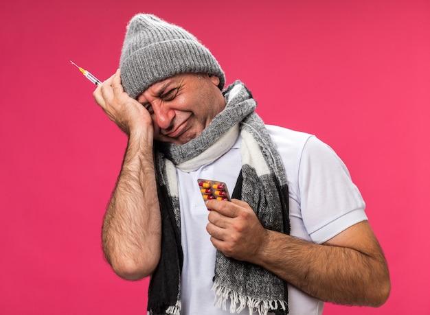 Smutny dorosły chory kaukaski mężczyzna z szalikiem na szyi w czapce zimowej trzymającej strzykawkę i blister z lekami odizolowany na różowej ścianie z miejscem na kopię
