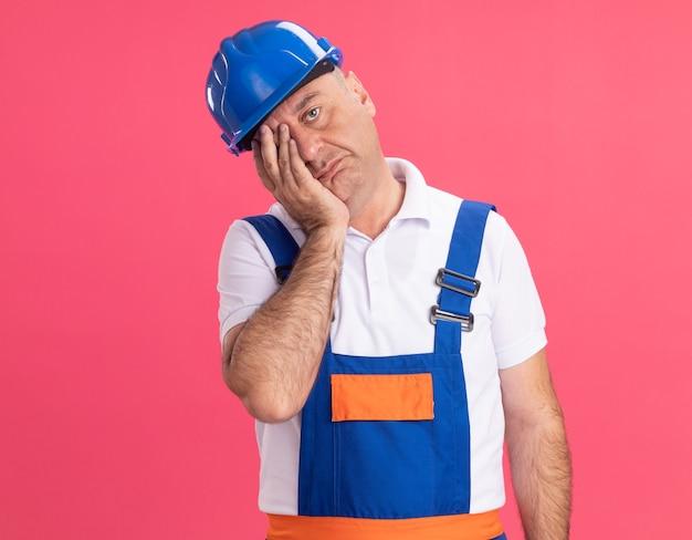 Smutny dorosły kaukaski mężczyzna budowniczy w mundurze kładzie rękę na twarzy na różowo