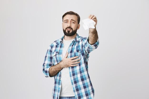 Smutny dorosły mężczyzna macha tkanką, żegnając się