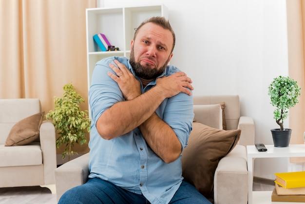 Smutny dorosły słowianin siedzi na fotelu krzyżuje ramiona kładąc ręce na ramieniu wewnątrz salonu