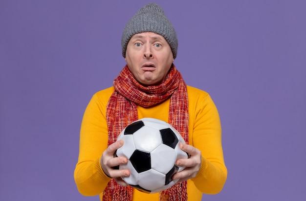 Smutny dorosły słowiański mężczyzna w czapce zimowej i szaliku na szyi, trzymający piłkę
