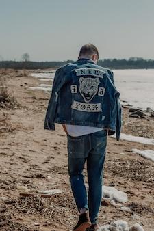 Smutny facet chodzi po plaży wczesną wiosną w dżinsach i dżinsach.
