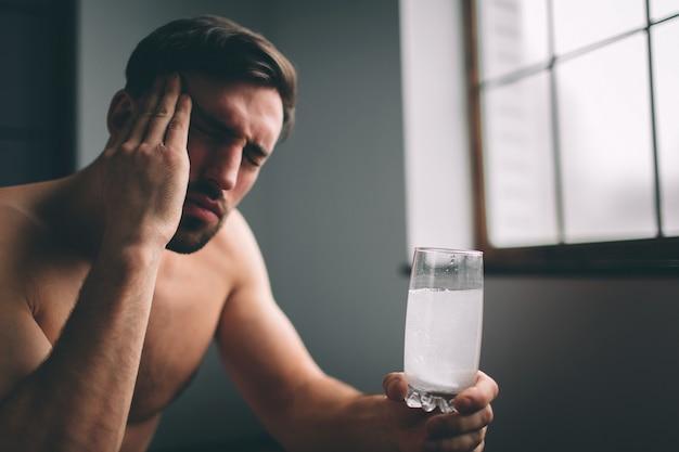 Smutny facet cierpi na kaca rano. nagi brodaty śpiący młody człowiek śpiący ze szklanką wody.