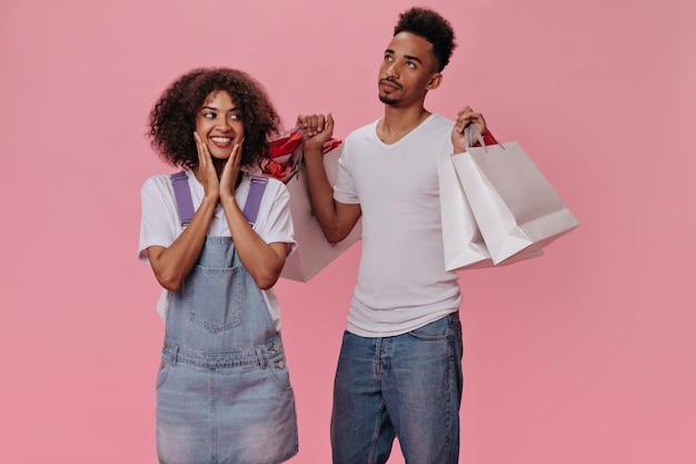 Smutny facet trzymający torby na zakupy swojej szczęśliwej dziewczyny na różowej ścianie