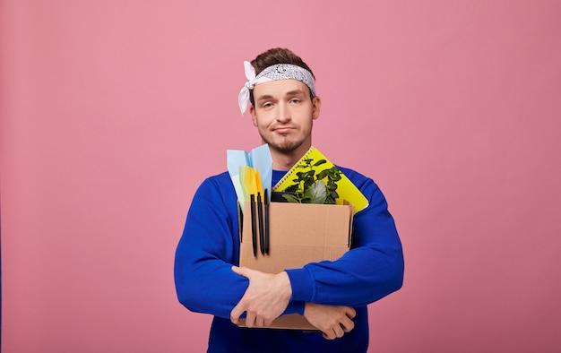 Smutny, fajny facet został zwolniony z pracy, ściska pudełko obiema rękami.