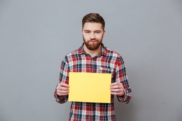 Smutny gniewny brodaty mężczyzna trzyma pustego papier